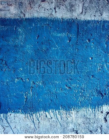The concrete wall in the city, the building is painted with blue paint, with fluid podges. Old building background of concrete wall.