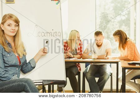 Education knowledge wisdom and learn new things concept - student girl writing Learning word on whiteboard in front of students her group mates in classroom