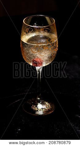 cherry in champagne wine in the bottom of a glass on a black velvet background