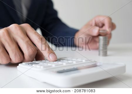 Businessman using calculator to analysis business investment and stacking coins arranged at office desk in modern office financial concept.