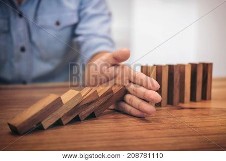Risk and strategy in business Close up of businessman hand stopping wooden block from falling in the line of domino.