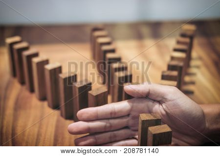 Risk and strategy in business Close up of businessman hand stopping wooden block between three way from falling in the line of domino.