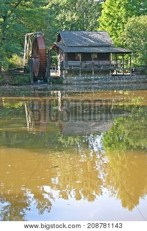 a restored gristmill with a large metal wheel, reflected in a pond