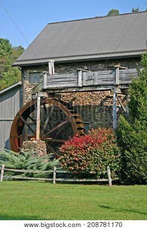 a stone gristmill, rusty waterwheel, and shrubbery