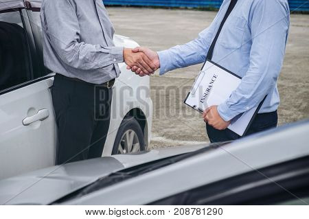 Insurance Agent and customer shaking hands Traffic Accident and insurance concept.