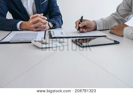Businessman will be signing a car insurance policy Agent man is holding the document and waiting for his reply to finish.