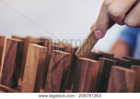 Team abstract business concept close up of business hand putting wooden block to complete in game.