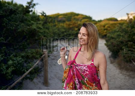 Attractive slender barefoot woman carrying her shoes as she walks along a sandy beach path smiling happily at the camera on summer vacation