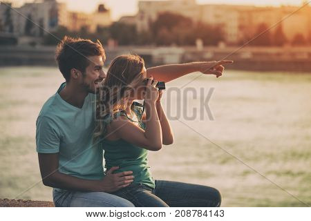 Young and beautiful happy couple photographing together.