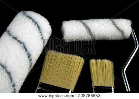 Decorating paint brushes and rollers isolated on a black background