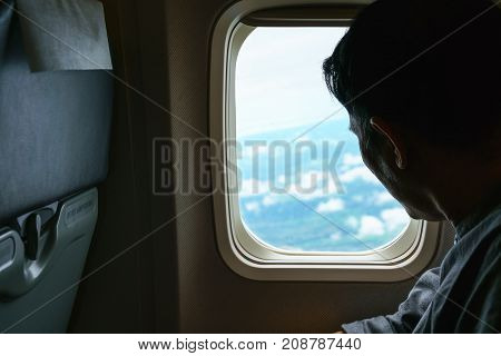 Middle-aged man looking out of airplane's window viewing Thailand's landscape below