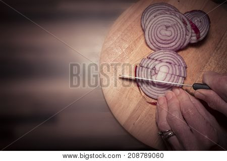 Cutting red onion vegetable in kitchen on chopping board