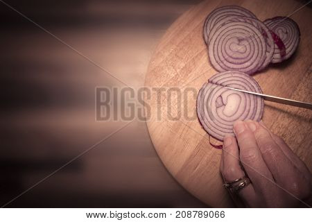 Cutting raw red onion in kitchen on chopping board with knife