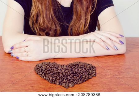 stacked female hands in front of the heart of coffee beans