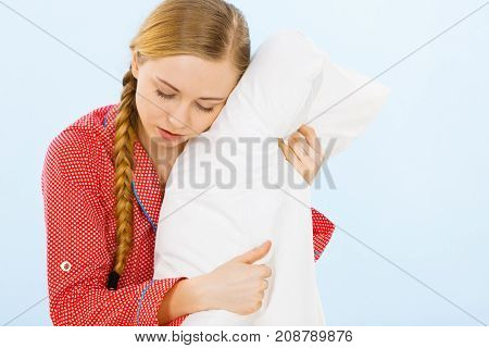 Young Woman Wearing Pajamas Hugging Soft Pillow