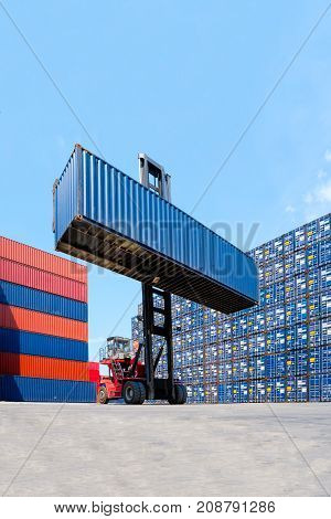 Forklift Truck Lifting Cargo Container In Shipping Yard Or Dock Yard With Cargo Container Stack In B