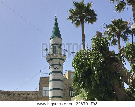 A white minaret with green roof in the Israeli city of Acre