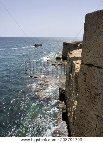 The city walls of Acre on the Mediterranean coast of Israel. It is a tourist boat on the sea