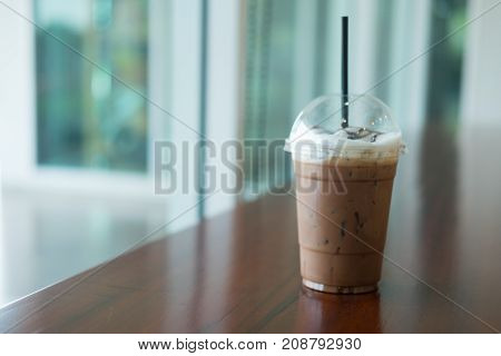 Iced coffee in takeaway cup on table. Selective focus