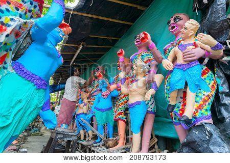 KUMARTULI KOLKATA INDIA - OCTOBER 10 2014 - Artist preparing clay idols of female demons to be used during Kali Puja worshipping of Goddess Kali Hindu festival of Deepavali or Diwali.