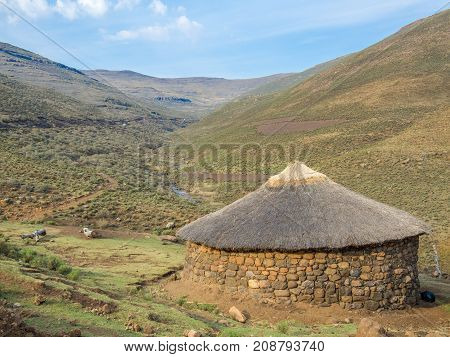 Traditional thatched stone round hut of the Basutho in the mountain highlands of Lesotho, Southern Africa.