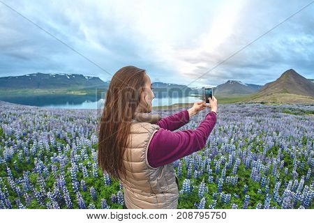 Girl in warm clothing standing in field of flowers on background of mountains and sea of Iceland and taking selfie using smartphone