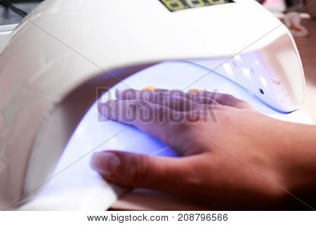 Closeup of the hand of a woman inside a UV or LED lamp, curing her recently applied gel nail polish at a salon