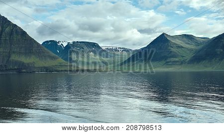 Travel to Iceland. beautiful sunrise over the ocean and fjord in Iceland. Icelandic landscape with mountains, sky and clouds. View of fjord near Flateyri, a village in the north-west of Iceland, on the Westfirdir peninsula