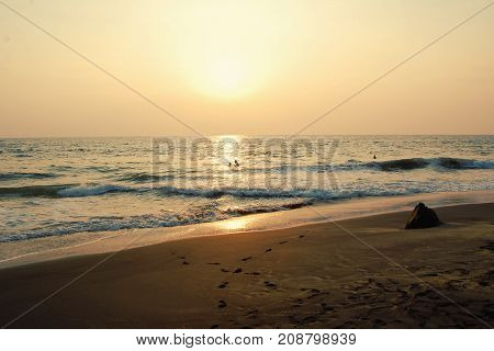 Tropical beach and peaceful ocean. Aged photo. Tourists enjoy the sea on sunset. Sunset on the Beach in Varkala Kerala India.