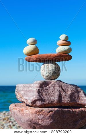 Symbolic scales of stones against the background of the sea and blue sky. Concept of harmony and balance. Pros and cons work - life concept