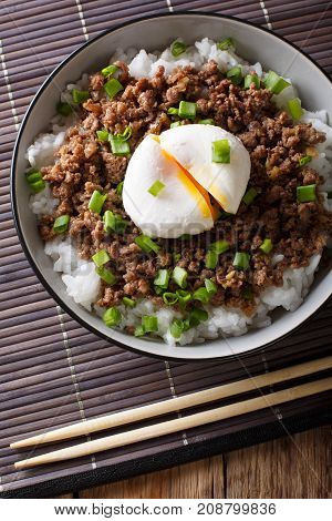 Japanese Dish: Spicy Meat Soboro With Egg Poached And Rice Close-up In A Bowl.vertical Top View