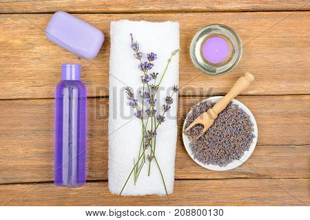 Shampoo shower gel liquid soap aromatic candle made from lavender flowers on a wooden surface