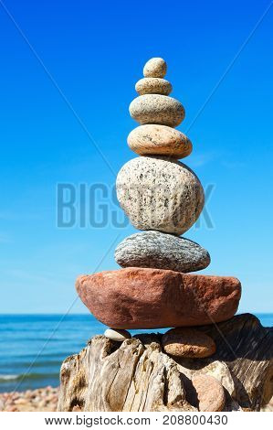 Stones balance on a background of blue sky and sea. Concept of balance and harmony