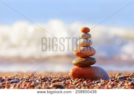 Pyramid of colorful balanced stones on the sea background. Concept of harmony and balance. Soft focus selective focus