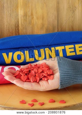 Female hand is holding many little hearts on a wooden background. Volunteer uniform in the background. Volunteering concept