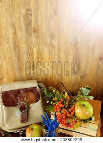 A backpack, school supplies and rowan berries on a wooden background. Back to school composition. Copy space. Sun ray glare imitation