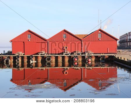 Red Fishermen Buildings in Winter with Reflection on Cold Water
