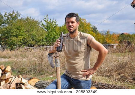 Tired lumberjack get rest and drink beer. Lumberjack drink cold beer to refresh after hard work