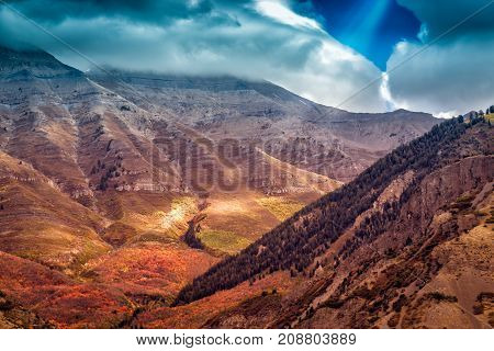 Beams of light shine through the clouds on a dramatic landscape made up of mountains and foothills on an autumn day in Utah