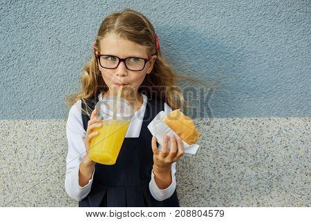 Cute smiling little schoolgirl holding a hamburger and orange juice outdoor - Back to school