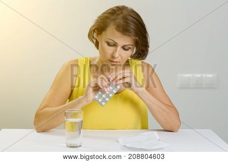 Woman holding pills in her hand taking pills. Health care and people concept