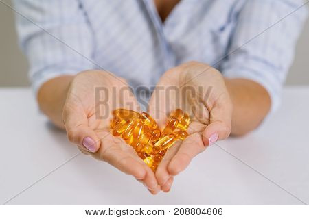 Hands of a woman holding fish oil Omega-3 capsules. Healthy eating medicine health care food supplements and people concept