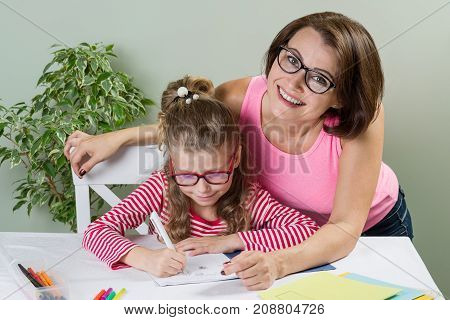 Mom helps her daughter elementary school pupil in her notebook at home at the table. Back to school concept.
