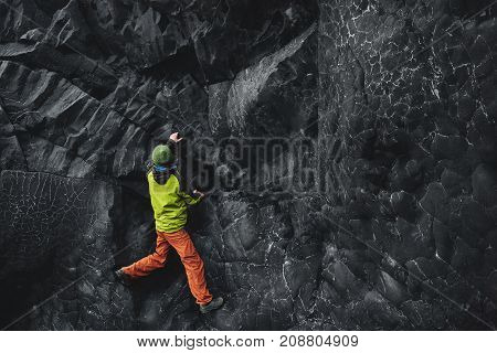 male rock climber. rock climber climbs on a black rocky wall on the ocean bank in Iceland, Kirkjufjara beach. man makes hard move without rope.