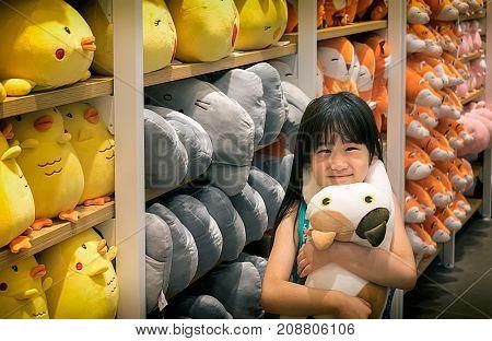 NONTHABURI THAILAND - OCTOBER 08: Japanese little girl Irisa Chujo hugs a Neko Atsume stuffed animal in MINIso gift shop located in CentralPlaza Westgate in Nonthaburi on October 06 2017.