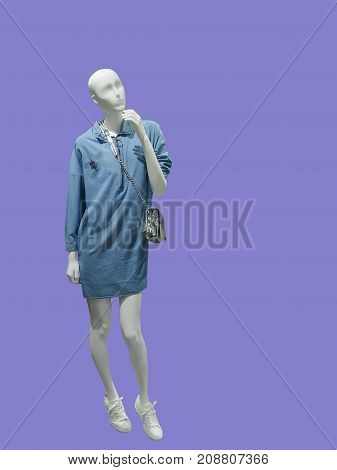 Full-length female mannequin wearing blue jeans dress isolated. No brand names or copyright objects.