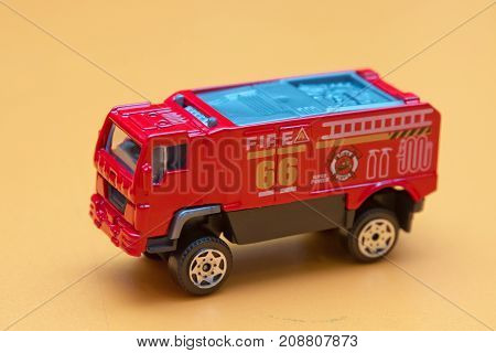 Red toy fire truck Toy fire engine extinguishes flaming house. Careless handling of fire dangerous for life