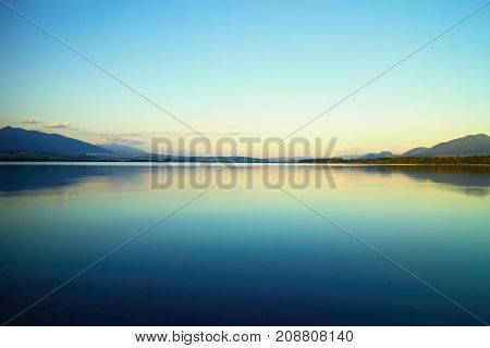 Beautiful scenery of sunset over Liptovska Mara. Water level, mirroring, sunlight and amazing view of Liptov in Slovakia.