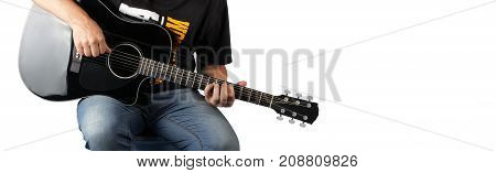 Music - fragment man play a black acoustic guitar on a white background.