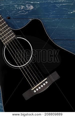 Musical instrument - Silhouette Black cutaway electric acoustic guitar on a dark blue wood background.